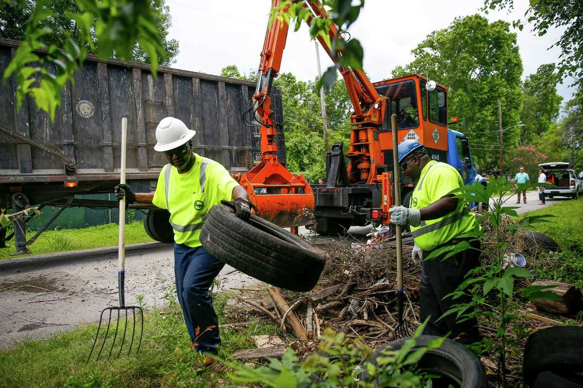 Solid Waste Management employees Dennis Bowen, left, and Avrin Mitchell help remove tires from an illegal dumping site on Wellington Road. City officials, including Mayor Sylvester Turner, held a press conference at the dump site to urge the governor to declare a disaster in order to help the city remove breeding grounds for mosquitos that could carry the zika virus Thursday, June 9, 2016 in Houston.