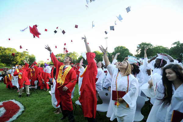 Graduates throw their caps into the air after receiving their diplomas at the Derby High School graduation ceremony Thursday at Leo F. Ryan Athletic Complex.