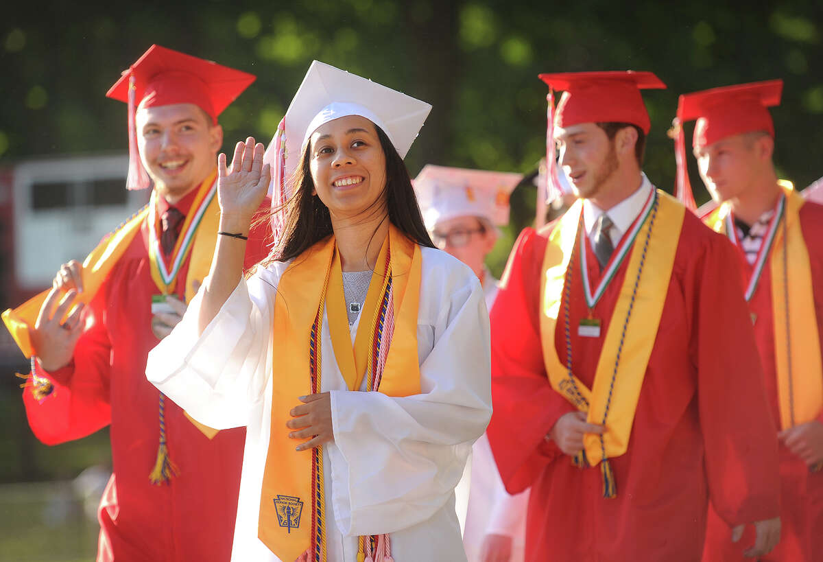 Salutatorian Brittany Santiago waves to her family as she walks in with her fellow graduates to the Derby High School graduation ceremony at Leo F. Ryan Athletic Complex in Derby, Conn. on Thursday, June 9, 2016.