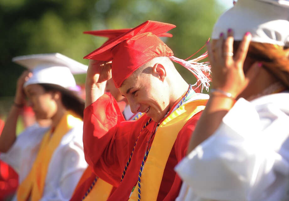 Graduate Zachary Cerreto grabs his cap to keep it from blowing off in the wind during the Derby High School graduation ceremony at Leo F. Ryan Athletic Complex in Derby, Conn. on Thursday, June 9, 2016. Photo: Brian A. Pounds / Hearst Connecticut Media / Connecticut Post