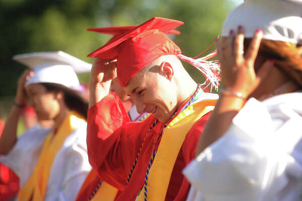Graduate Zachary Cerreto grabs his cap to keep it from blowing off in the wind during the Derby High School graduation ceremony at Leo F. Ryan Athletic Complex in Derby, Conn. on Thursday, June 9, 2016.