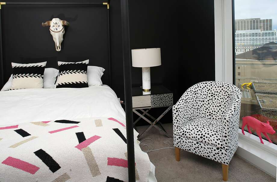 Style blogger Rebecca La Prade's bedroom by interior designer Michael Hilal, who gave one wall a matte-black treatment. He lightens it up with a polka-dot chair from One Kings Lane. Photo: Liz Hafalia, The Chronicle