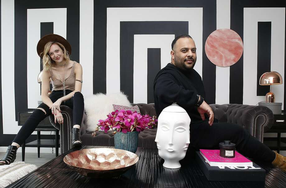 Style blogger Rebecca La Prade and interior designer Michael Hilal in LaPrade's living room in her apartment in the Mid-Market Nema building. Hilal created the bold graphic wall and suggested the bold black Bernhardt coffee table. Photo: Liz Hafalia, The Chronicle