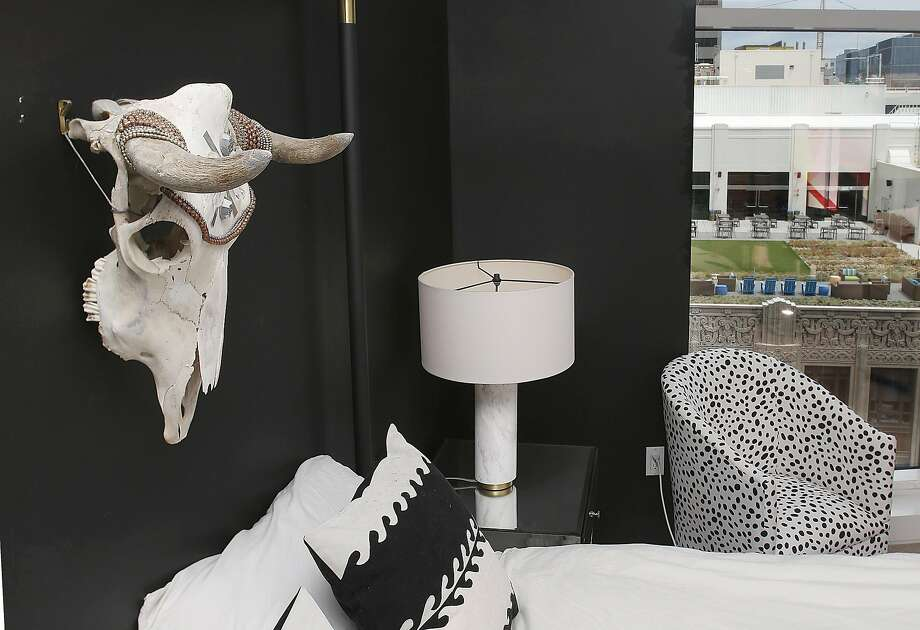 A Vanessa Mooney skull is the highlight on a black-matte wall in the bedroom of style blogger Rebecca La Prade's Mid-Market apartment decorated by Michael Hilal. The polka-dot chair is from One Kings Lane. The window shows a view of Twitter's patio. Photo: Liz Hafalia, The Chronicle