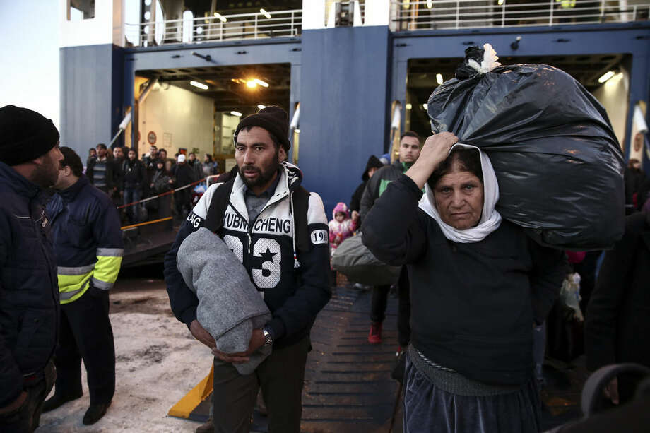 In this photo taken on Tuesday, Dec. 29, 2015, migrants and refugees disembark from a ferry after their arrival from Greek eastern Aegean islands to the port of Piraeus, near Athens. More than a million people fleeing war or poverty at home reached European countries in 2015 in the largest refugee influx the continent has seen since the end of World War II _ a crisis that has tested European unity and pressured the vision of a borderless continent. Greece, the European Union's most financially troubled member, has borne the brunt of the exodus with more than 850,000 people reaching the country's shores, nearly all arriving on Greek islands from the nearby Turkish coast. (AP Photo/Yorgos Karahalis)