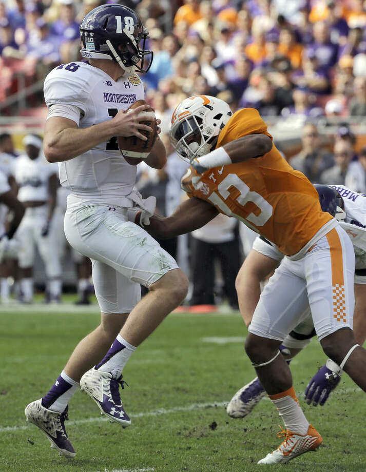 Northwestern quarterback Clayton Thorson (18) gets spun around by Tennessee defensive back Malik Foreman (13) during the first quarter of the Outback Bowl NCAA college football game, Friday, Jan. 1, 2016, in Tampa, Fla. (AP Photo/Chris O'Meara)