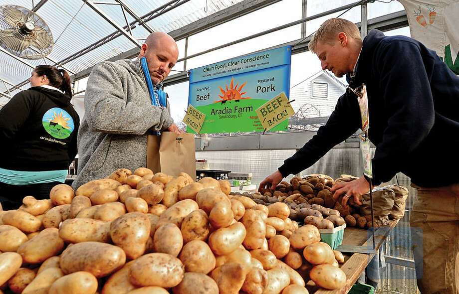 Hour photo / Erik Trautmann Ryan Cornish picks out some potatoes from Simo Ziegler at Riverbank Farms during the Westport Winter Farmer's Market at Gilbertie's Herb Gardens Saturday.
