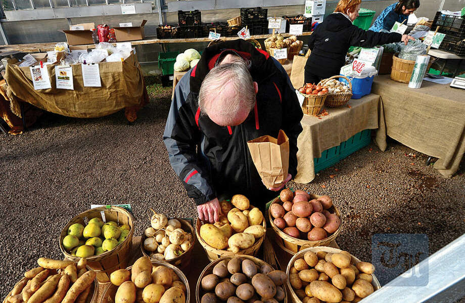 Hour photo / Erik Trautmann Customers peruse the produce during the Westport Winter Farmer's Market at Gilbertie's Herb Gardens Saturday.