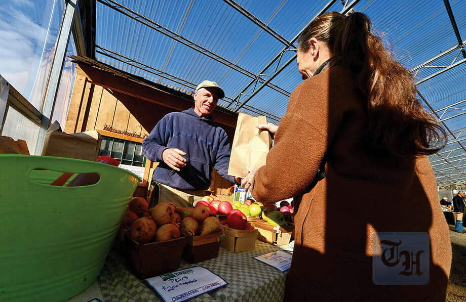 Hour photo / Erik Trautmann Pete Teveris of Woodland Farms serves customers during the Westport Winter Farmer's Market at Gilbertie's Herb Gardens Saturday.