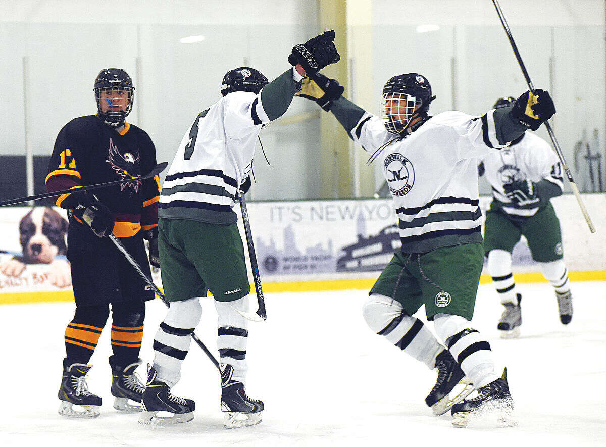 Hour photo/John Nash -Norwalk-Brien McMahon co-op skaters Matt Cavanagh, left, and Kevin Remson, right, celebrate their team's first goal in Saturday's 4-1 win over the Eastern Connecticut Eagles at the SoNoIce House.