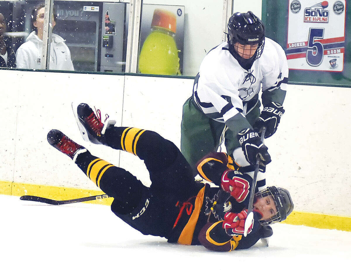 Hour photo/John Nash Norwalk-McMahon's Stephen Pare, top, gets tangled up with Eastern Connecticut Eagles player Ryan Brandt during Saturday's Division 3 hockey game at the SoNoIce House in Norwalk. The host co-oppers got their first win of the season with a 4-1 win.