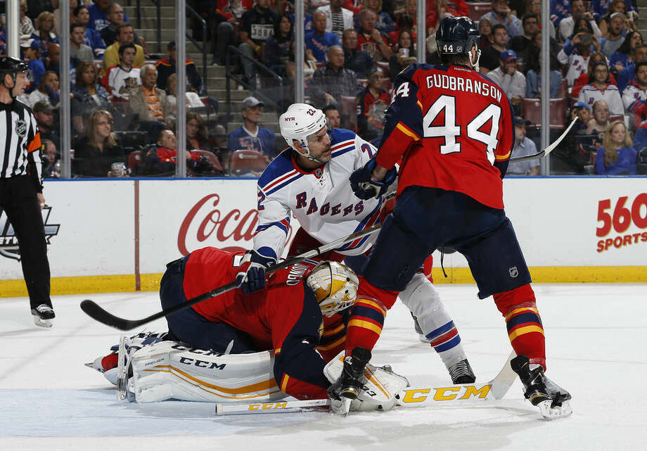Florida Panthers defenseman Erik Gudbranson (44) checks New York Rangers defenseman Dan Boyle (22) as Panthers goaltender Roberto Luongo (1) defends the net during the second period of an NHL hockey game, Saturday, Jan. 2, 2016, in Sunrise, Fla. (AP Photo/Joel Auerbach)