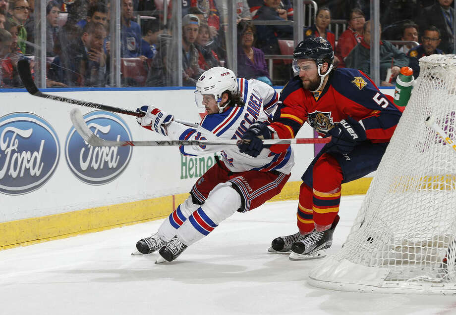 New York Rangers forward Mats Zuccarello (36) and Florida Panthers defenseman Aaron Ekblad (5) chase a loose puck as they skate behind the net during the second period of an NHL hockey game, Saturday, Jan. 2, 2016, in Sunrise, Fla. (AP Photo/Joel Auerbach)