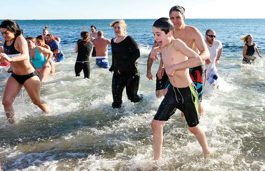 Hour photo / Erik Trautmann Polar Plunge participants exit the water at Compo Beach in Westport Thursday during the 8th Annual Temple Israel (TI) Polar Bears Plunge to benefit the Child Guidance Center of Mid-Fairfield County. The other polar plunge held Thursday was organized by Team Mossman and raised money for the Save the Children.