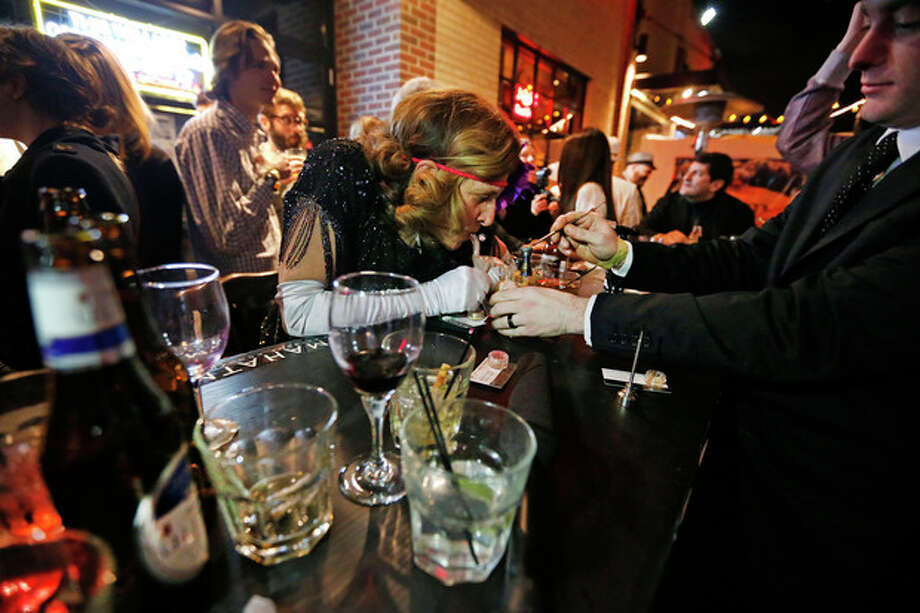 A server, right, behind an outdoor bar prepares marijuana for partygoers to smoke during a Prohibition-era themed New Year's Eve party celebrating the start of retail pot sales, at a bar in Denver, late Tuesday Dec. 31, 2013. Colorado is to begin marijuana retail sales on Jan. 1, a day some are calling 'Green Wednesday.' (AP Photo/Brennan Linsley) / AP
