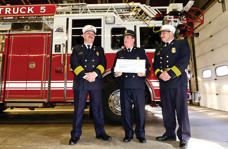 Wilton Fire Chief Ronald Kanetrman and Deputy Fire Chief Mark Amatrudo receive a $4,000 check from Jack Murphy, charter president of the Bergen County Fire Chiefs Association and chairman of the New York City High-Rise Fire Safety Directors Association, to be donated to the National Fallen Firefighters Foundation.