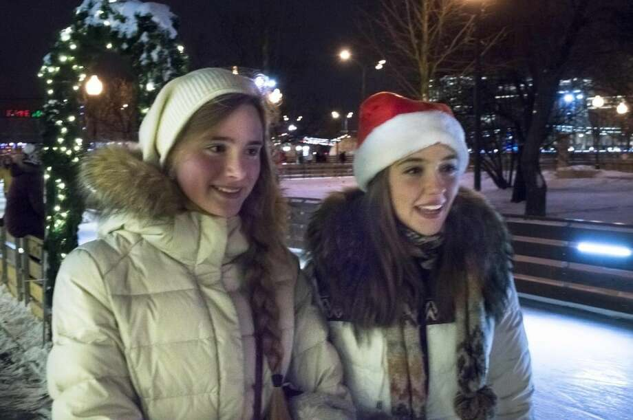 In this photo taken on Sunday, Dec. 28, 2014, Students Elizaveta Kozlova, left, and Anastasia Khripunova speak to the Associated Press at the Gorky Park skating rink in Moscow, Russia. Both said that they're looking forward with high optimism to 2015 as they take a rest. Although Russia faces a challenging year as the ruble takes a sharp fall and tensions with the West soar, many Russians appear to be taking the troubles as a call to pull together and redouble their energies. (AP Photo/Jim Heintz)