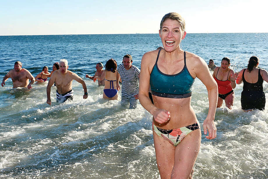 Hour photo / Erik Trautmann Sandy Earley exits the water after taking part in the 11th Annual Team Mossman Polar Plunge to benefit Save the Children at Compo Beach in Westport Thursday. The second polar plunge Thursday by Westport Temple Israel raised over $70,000 for the Child Guidance Center of Mid-Fairfield County.