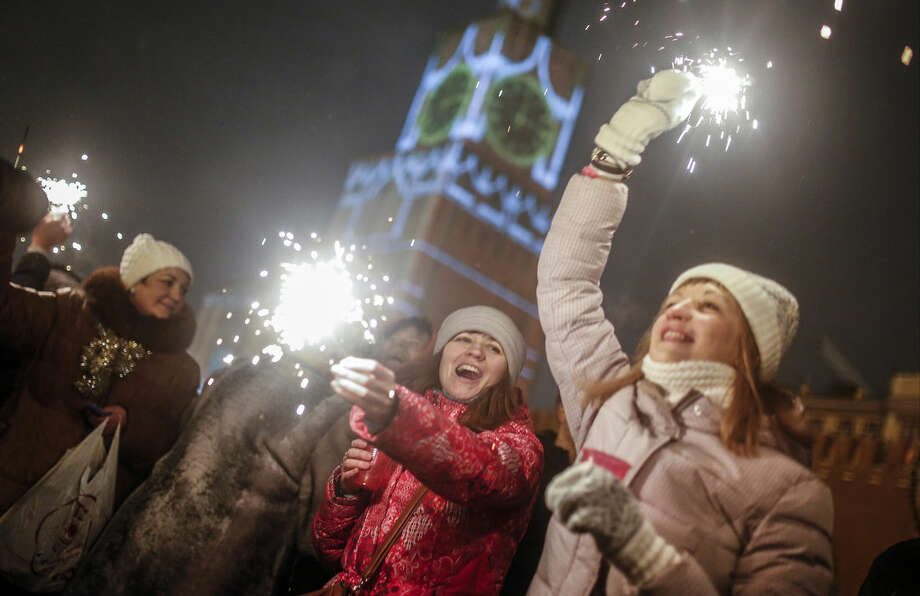People light sparklers as they celebrate the New Year at the Red Square in Moscow, Russia, Thursday, Jan. 1, 2015. (AP Photo/Denis Tyrin)
