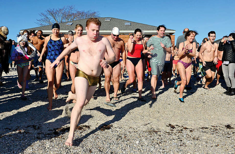 Hour photo / Erik Trautmann Seamus Keating races into the water at Compo Beach in Westport Thursday during the 8th Annual Temple Israel (TI) Polar Bears Plunge to benefit the Child Guidance Center of Mid-Fairfield County. The other polar plunge held Thursday was organized by Team Mossman and raised money for the Save the Children.