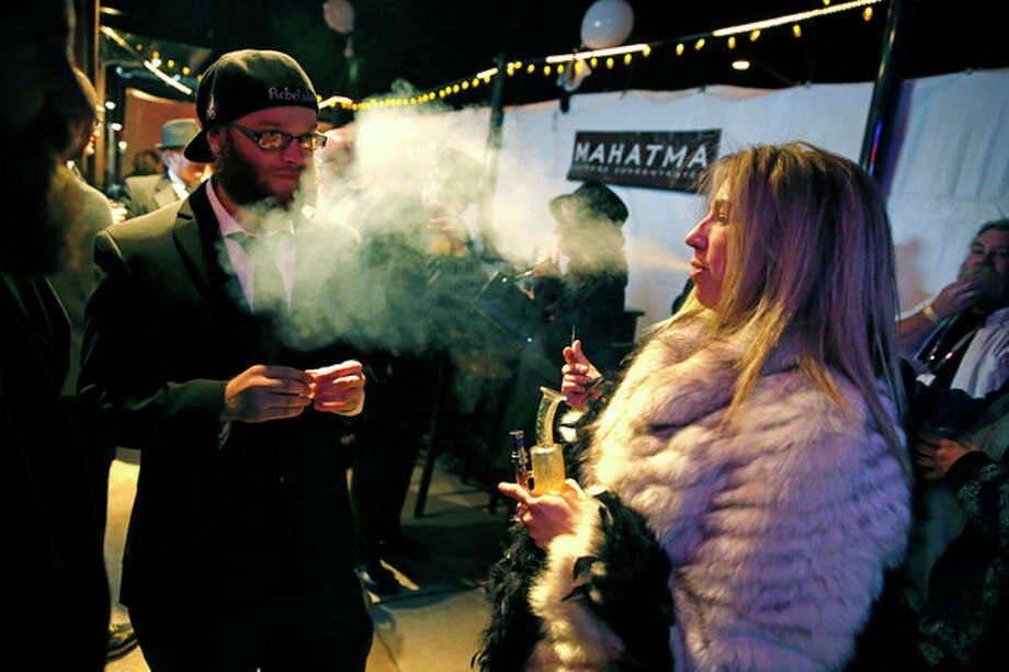 Sheri Foster, of Denver, smokes marijuana during a Prohibition-era themed New Year's Eve party celebrating the start of retail pot sales, at a bar in Denver, late Tuesday Dec. 31, 2013. Colorado is to begin marijuana retail sales on Jan. 1, a day some are calling 'Green Wednesday.' (AP Photo/Brennan Linsley) / AP