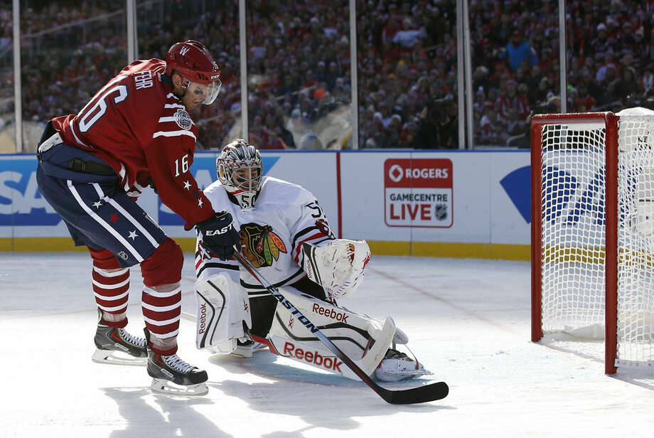 Washington Capitals right wing Eric Fehr (16) scores a goal past Chicago Blackhawks goalie Corey Crawford (50) in the first period of the Winter Classic outdoor NHL hockey game at Nationals Park, Thursday, Jan. 1, 2015, in Washington. (AP Photo/Alex Brandon)