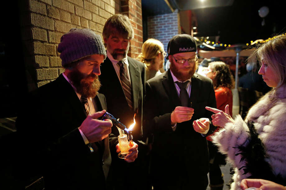 Partygoers smoke marijuana during a Prohibition-era themed New Year's Eve party celebrating the start of retail pot sales, at a bar in Denver, late Tuesday Dec. 31, 2013. Colorado is to begin marijuana retail sales on Jan. 1, a day some are calling 'Green Wednesday.' (AP Photo/Brennan Linsley) / AP