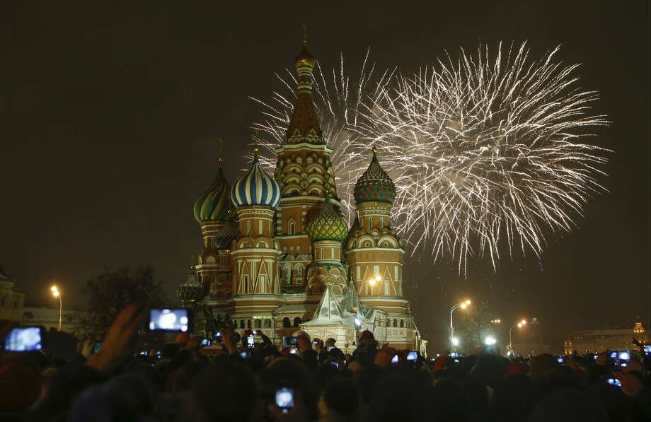 Fireworks explode over St.Basil's Cathedral as people celebrate the New Year at the Red Square in Moscow, Russia, Thursday, Jan. 1, 2015. (AP Photo/Denis Tyrin)