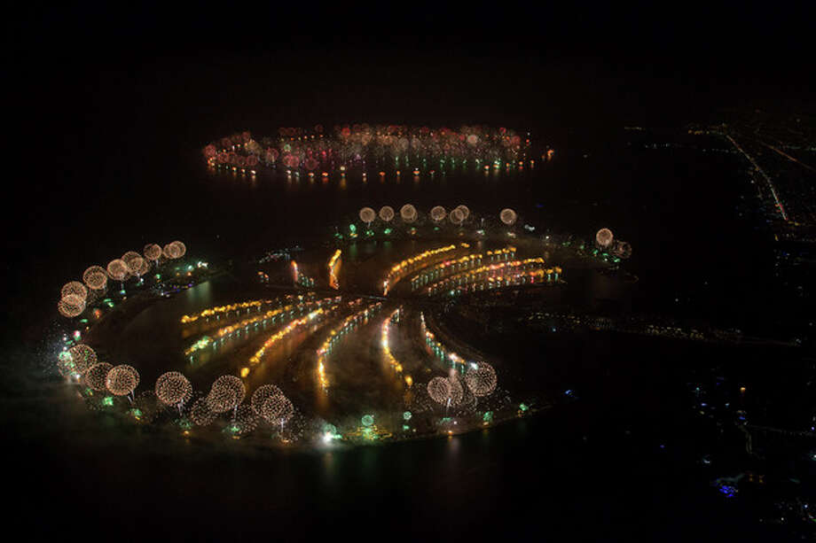 "In this photo provided by Dubai World Record 2014, fireworks explode over Palm Jumeirah Island, front, and World Islands, rear, to celebrate the New Year on Wednesday, Jan. 1, 2014 as the city attempts to breaks the Guinness World Record for the ""Largest Firework Display."" (AP Photo/Dubai World Record 2014, Simon Brooke-Webb) / Dubaiworldrecord2014"