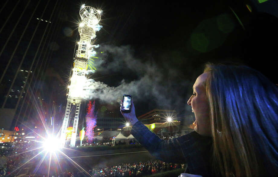 Stephanie Weaver snaps photos of the Peach Drop at Underground Atlanta, early on New Year's Wednesday, Jan. 1, 2014, in Atlanta. (AP Photo/Atlanta Journal-Constitution, Curtis Compton) GWINNETT OUT MARIETTA OUT LOCAL TV OUT (WXIA, WGCL, FOX 5) / Atlanta Journal & Constitution
