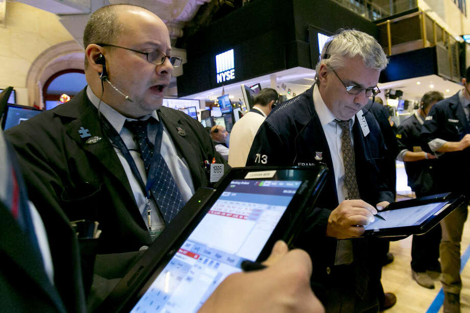 Trader Jeffrey Vazquez, left, works on the floor of the New York Stock Exchange, Wednesday, Jan. 6, 2016. Stocks are opening lower as investors fret about signs of belligerence in North Korea and more weakening of China's economy. (AP Photo/Richard Drew)
