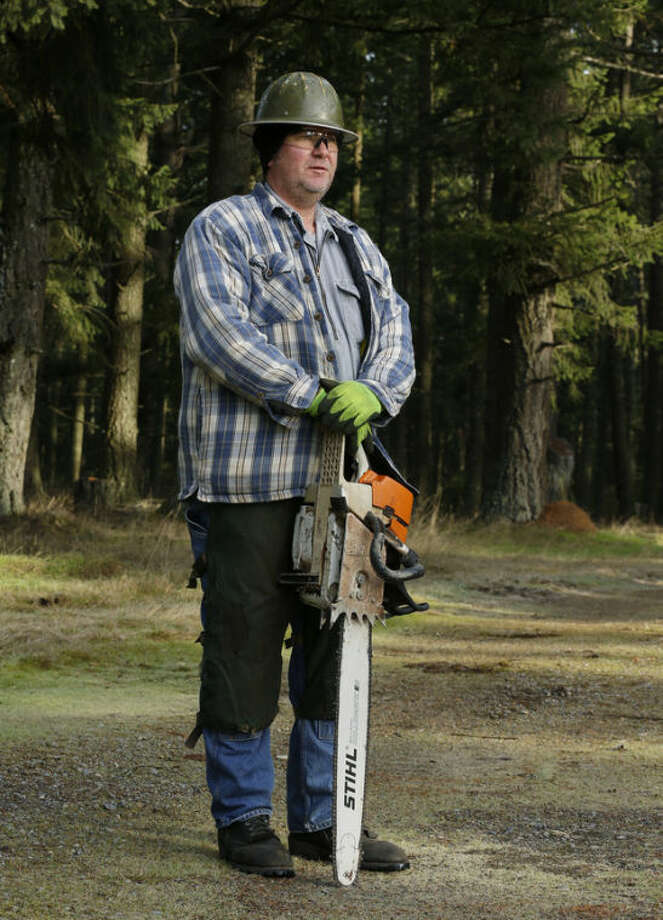 Tom Edwards poses for a portrait with his chain saw and logging clothes, Thursday, Dec. 19, 2013 in the woods near Spanaway, Wash. Edwards was not cutting trees the day the photo was taken, and work has been slow this season for him. Despite working as a logger all his life, he is pessimistic about his chances of ever retiring, an opinion common among blue-collar baby boomers in the U.S. (AP Photo/Ted S. Warren)