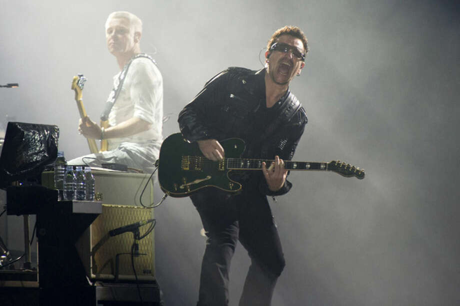 FILE - In this July 20, 2011 file photo, Bono, right, and Adam Clayton, from the rock group U2, perform in concert as part of U2's 360 Tour at the New Meadowlands Stadium in East Rutherford, N.J. Bono wrote on the band's website Thursday Jan. 1, 2015, he may never play guitar again due to injuries suffered in a New York City cycling accident in November. (AP Photo/Charles Sykes, file)