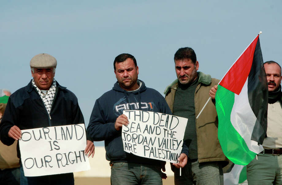 Palestinians hold placards and a national flag near Israeli border police during a demonstration over a proposed Israeli bill seeking to annex the Jordan valley, near the West Bank town of Jericho, Wednesday, Jan. 1, 2014. Israeli hard-liners, including members of Israeli Prime Minister Benjamin Netanyahu's Likud Party, have said the West Bank's Jordan Valley, a strategic area along the border with Jordan, must be annexed by Israel. The Palestinians said they couldn't establish a viable state without the valley, which makes up one-fifth of the West Bank. (AP Photo/Majdi Mohammed) / AP