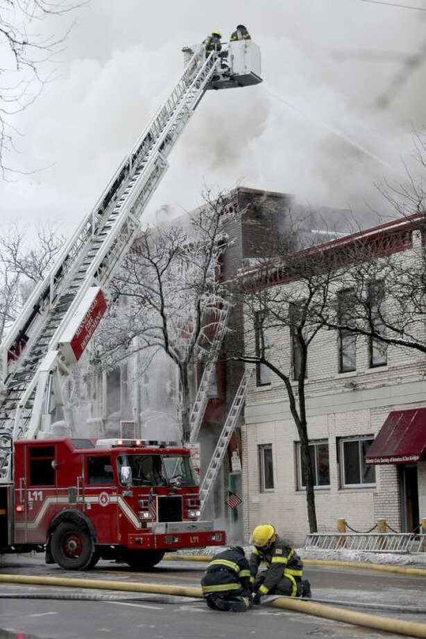 Firefighters work the scene where a fire engulfed several apartment units in the Cedar Riverside neighborhood, in Minneapolis, Wednesday, Jan. 1, 2014. Authorities say at least 13 people have been hurt. (AP Photo/Star Tribune, Elizabeth Flores)