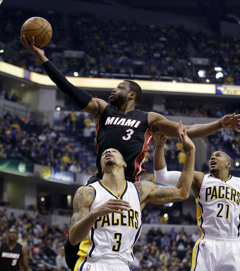 Miami Heat's Dwyane Wade, top, puts up a shot against Indiana Pacers' George Hill during the first half of an NBA basketball game Wednesday, Dec. 31, 2014, in Indianapolis. (AP Photo/Darron Cummings)