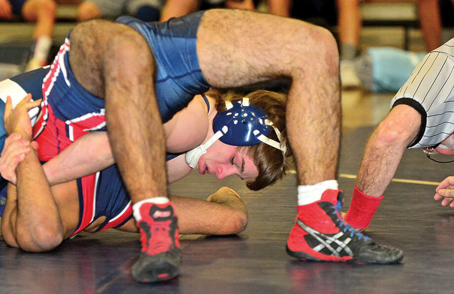 Hour photo / Erik Trautmann Wilton High School wrestler Zach Zeyher pins Brien McMahon's Felipe Silva during their 160 lb bout Wednesday night in Wilton.