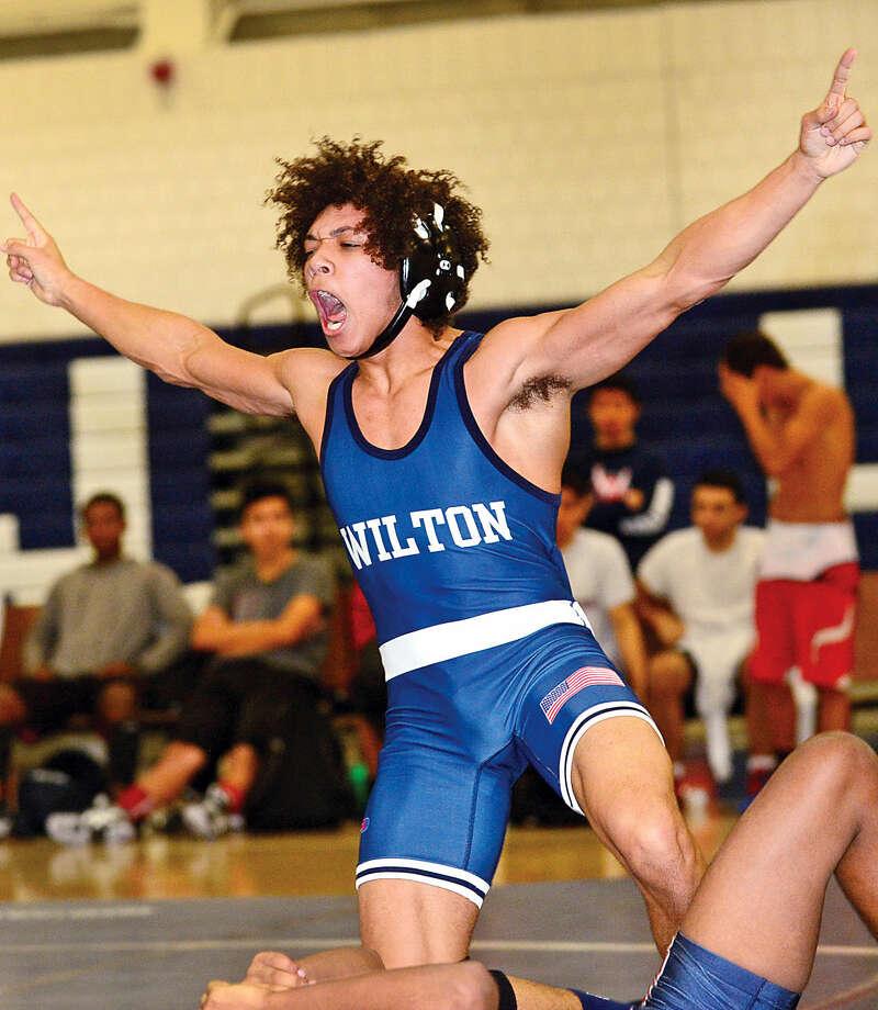 Hour photo / Erik Trautmann Wilton High School wrestler Quinn Reedy takes on Brien McMahon's Josh Wyclif during their 132 lb bout in Wilton Wednesday night.