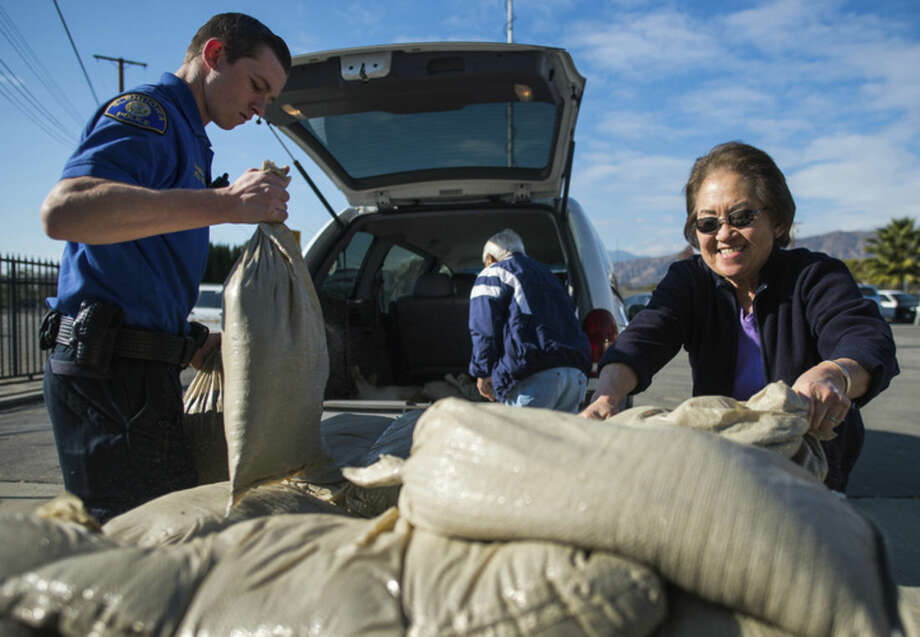 Residents Carrie Osato, right, and husband Mas Osato, back pick up sandbags from the Glendora City Yard while being assisted by Glendora cadet Matt Wending, left, as Southern California prepares for the El Nino in Glendora, Calif., Monday, Jan. 4, 2016. (Watchara Phomicinda/San Gabriel Valley Tribune via AP) MAGS OUT; NO SALES; MANDATORY CREDIT