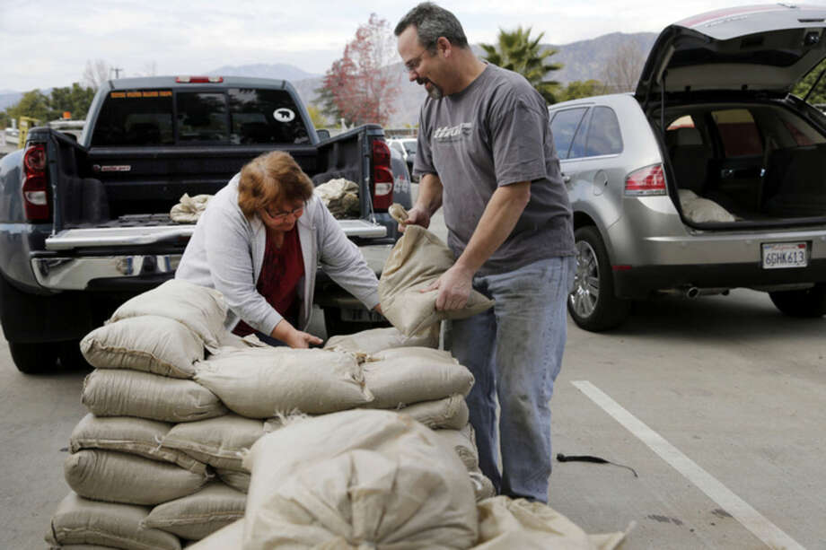 Residents Trina Gonzalez, left, and Todd Peterson stockpile sandbags to protect their homes from the rain in Glendora, Calif., Monday, Jan. 4, 2016. After all the talk, El Nino storms have finally lined up over the Pacific and started soaking drought-parched California with rain expected to last for most of the next two weeks, forecasters said Monday. (AP Photo/Nick Ut)