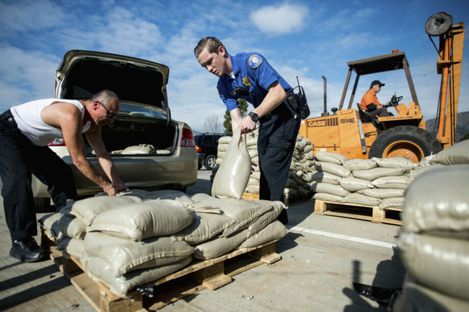 Glendora Police cadet Matt Wending, center, helps resident Frank Salazar with loading sandbags to his to car at Glendora City Yard, in Glendora, Calif., on Monday, Jan. 4, 2016, as Southern California prepare for the El Nino. The brewing El Niño system — a warming in the Pacific Ocean that alters weather worldwide — is expected to impact California and the rest of the nation in the coming weeks and months. (Watchara Phomicinda/San Gabriel Valley Tribune via AP) MAGS OUT; NO SALES; MANDATORY CREDIT