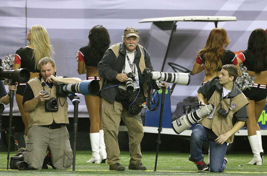 In this Sunday, Dec. 29, 2013, photo, AP Photographer Dave Martin, second from right, works during the first half of an NFL football game between the Carolina Panthers and the Atlanta Falcons, in Atlanta. Martin, a longtime Associated Press photographer based in Montgomery, Ala., died after collapsing on the Georgia Dome field at the Chick-fil-A Bowl on Tuesday, Dec. 31, 2013. Martin was 59. (AP Photo/John Bazemore) / AP