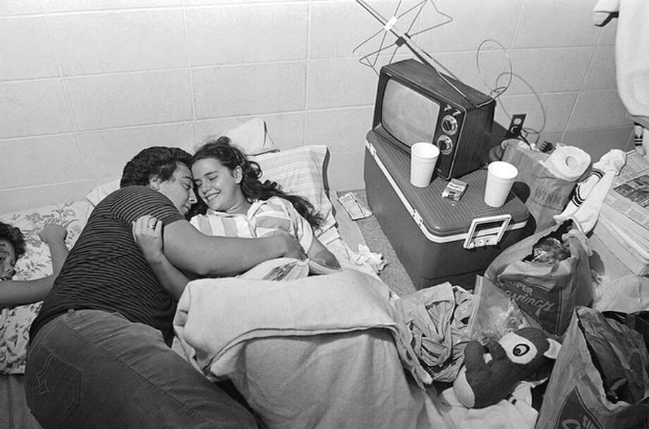FILE - In this Friday, Aug. 30, 1985, file photo taken by Dave Martin, Mark Bailey holds his fiance Belinda Mammack as they relax in an emergency shelter at Theodore High School, Ala. Martin, a longtime Associated Press photographer based in Montgomery, Ala., died after collapsing on the Georgia Dome field at the Chick-fil-A Bowl on Tuesday, Dec. 31, 2013. Martin was 59. (AP Photo/Dave Martin, File) / AP