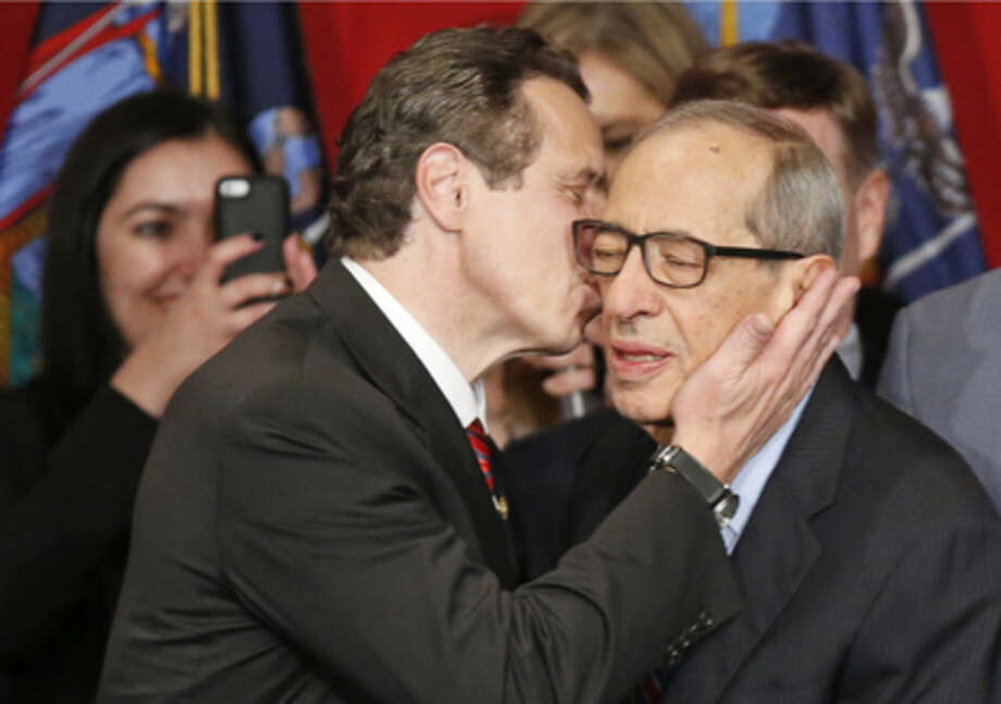 FILE - In this Nov. 4, 2014, file photo, New York Gov. Andrew Cuomo kisses his father, Mario Cuomo, as he celebrates after defeating Republican challenger Rob Astorino, at Democratic election headquarters in New York. Andrew Cuomo is the first New York state Democratic governor since his father to win re-election in the state. Cuomo died Thursday, Jan. 1, 2015, the day Andrew started his second term as governor, the New York governor's office confirmed. He was 82. (AP Photo/Kathy Willens)