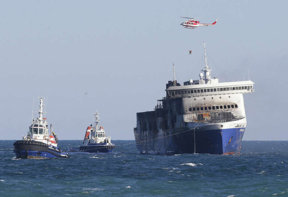 The Norman Atlantic ferry is being towed into the port of Brindisi, Italy, Friday, Jan. 2, 2015. The blaze that broke out Sunday and torched the ferry has killed at least 11 people and authorities prepared to search it for possible more dead. Italy says 477 people were rescued, most by helicopters that plucked survivors off the top deck in gale-force winds and carried them to nearby boats. (AP Photo/Antonio Calanni)