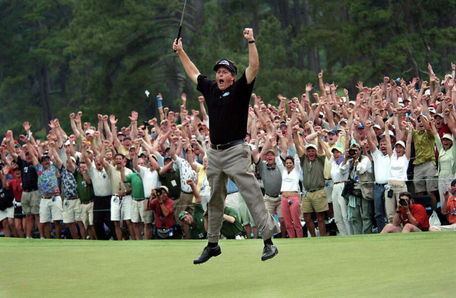 FILE - In this April 11, 2004, file photo, taken by Dave Martin, Phil Mickelson celebrates after winning the Masters golf tournament with at the Augusta National Golf Club in Augusta, Ga. Martin, a longtime Associated Press photographer based in Montgomery, Ala., died after collapsing on the Georgia Dome field at the Chick-fil-A Bowl on Tuesday, Dec. 31, 2013. Martin was 59.(AP Photo/Dave Martin, File) / AP