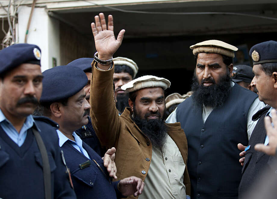 Pakistani police officers escort Zaki-ur-Rahman Lakhvi, center, the main suspect of the Mumbai terror attacks in 2008, after his court appearance in Islamabad, Pakistan, Thursday, Jan. 1, 2015. Lakhvi was sent to judicial remand in an abduction case by a court, official said. (AP Photo/B.K. Bangash)