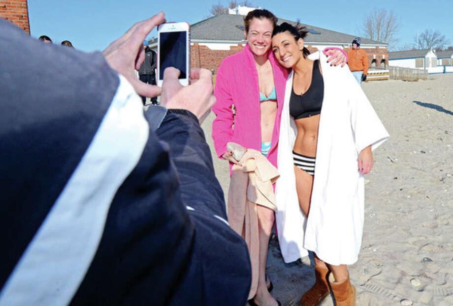 "Hour photo / Erik Trautmann Area residents including Christine Finerty and Sarah Beke brave the cold to participate in the ""polar plunge"" to benefit the Make-A-Wish foundation at Compo Beach in Westport Wednesday. / (C)2013, The Hour Newspapers, all rights reserved"