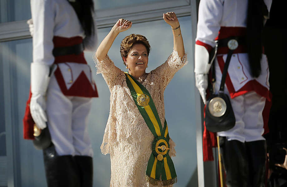 Wearing the green-and-gold presidential sash, Brazil's President Dilma Rousseff gestures during her inauguration, from the Planalto presidential palace in Brasilia, Brazil, Thursday, January 1, 2015. Rousseff was sworn into her second term in office Thursday, confronting less congressional support for her ruling coalition.(AP Photo/Leo Correa)