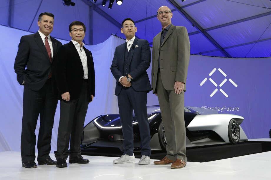 Nevada Gov. Brian Sandoval, left, poses for a photo in front of the FFZero1 by Faraday Future, alongside members of the Faraday Future team at CES Unveiled, a media preview event for CES International Monday, Jan. 4, 2016, in Las Vegas. The high-performance electric concept car was unveiled during a news conference by Faraday Future. From right are Nick Sampson, product developer, Richard Kim, head of global design, Ding Lei, and letv co-founder. (AP Photo/Gregory Bull)